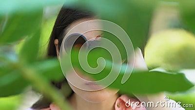 Κατασκοπεύοντας νεαρές γυναίκες που κοιτούν μέσα από τα κιάλια που στέκονται ανάμεσα στα δέντρα, το ενδιαφέρον φιλμ μικρού μήκους