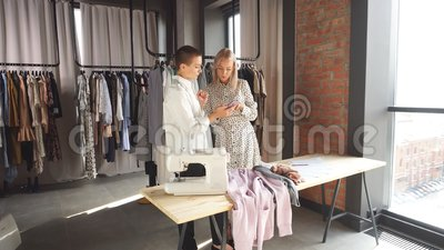 Καυκάσιος σχεδιαστής μόδας συζητά με μοντέλο νέα ρούχα φιλμ μικρού μήκους