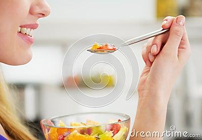 Κινηματογράφηση σε πρώτο πλάνο στην ευτυχή νέα γυναίκα που τρώει τη σαλάτα φρούτων