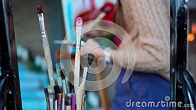 Κλείστε αυξημένος των βρώμικων βουρτσών, στο υπόβαθρο μια γυναίκα χρωματίζει μια εικόνα απόθεμα βίντεο
