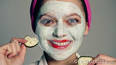 Κλείστε επάνω ενός κοριτσιού με μια μάσκα στο πρόσωπό της και μια πετσέτα στο κεφάλι της που κλείνει τα μάτια της με τα αγγούρια  απόθεμα βίντεο
