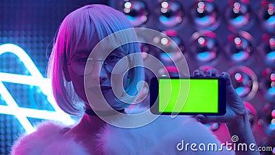 Κομψή γυναίκα που κρατά το κινητό τηλέφωνο με την πράσινη οθόνη κλειστή απόθεμα βίντεο