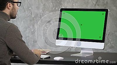 Κομψός επιχειρηματίας που αναλύει τα στοιχεία στην αρχή στον υπολογιστή του Πίσω άποψη στο όργανο ελέγχου Πράσινη επίδειξη προτύπ απόθεμα βίντεο