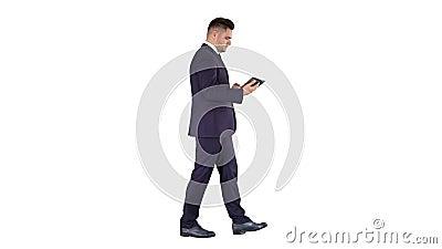 Κομψός νεαρός επιχειρηματίας που χρησιμοποιεί το tablet του υπολογιστή ενώ περπατάει σε λευκό φόντο φιλμ μικρού μήκους