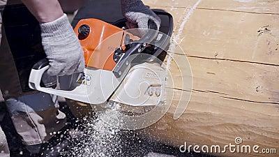Κοντινό πλάνο ανθρώπου που πριονίζει ηλεκτρικό πριόνι Αποκοπή Πριόνια από ξυλουργούς καθαρισμένη δοκό για κατασκευή με ξύλινη κατ φιλμ μικρού μήκους