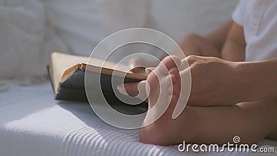Κοντινό πλάνο ενός βιβλίου κοντά στο πόδι ενός παιδιού Η μαμά διαβάζει ένα βιβλίο σε ένα παιδί φιλμ μικρού μήκους