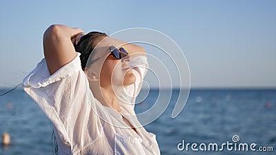 Κοντινό πλάνο, ευχάριστη ξεθωριασμένη κοπέλα με λευκό πουκάμισο που σηκώνει το χέρι απολαμβάνοντας ελευθερία στο θαλάσσιο περιβάλ απόθεμα βίντεο