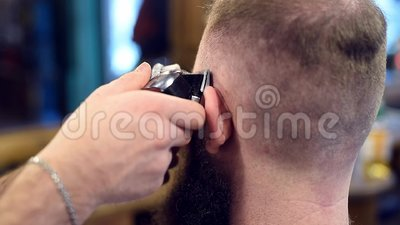 Κοντινό πλάνο μηχανήματος ψαλιδίσματος μαλλιών σε σφιχτά χέρια κάνοντας αντρικό στυλ μαλλιών Τρίχωμα κοντά στο αυτί, τρίψιμο που  φιλμ μικρού μήκους