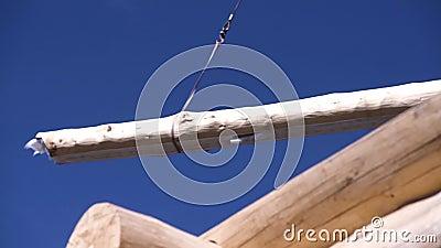 Κοντινό πλάνο ξύλινου σπιτιού και ανυψωτικός γερανός με ξυλεία Αποκοπή Ξύλινο σπίτι υπό κατασκευή στο φόντο του γερανού φιλμ μικρού μήκους