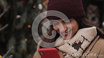 Κοντινό πλάνο χαμογελαστού αρκετά καυκάσου κοριτσιού στο Winter Hat και Mittens με το smartphone της, κοιτάζοντας την οθόνη απόθεμα βίντεο
