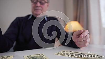 Κοντινό πλάνο ώριμων αντρών Καυκάσιων χεριών που μετράνε μετρητά και βάζουν χρήματα σε ξεχωριστές δέσμες Θολή συνταξιούχος απόθεμα βίντεο