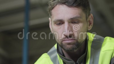 Κοντινό πορτρέτο σοβαρού Καυκάσου με πράσινο γιλέκο που κοιτάζει κάτω Επαγγελματίας εργαζόμενος σε εργοστάσιο παραγωγής απόθεμα βίντεο