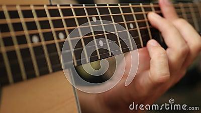 Κοντινό τζακί κιθάρας Τα δάχτυλα του άντρα αγγίζουν τις χορδές της κιθάρας Μουσική και χόμπι απόθεμα βίντεο