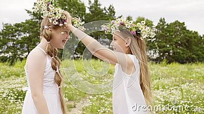 Κορίτσι δύο που φορά το floral στεφάνι που έχει τη διασκέδαση στο ανθίζοντας λιβάδι στη θερινή ημέρα Ευτυχές παιχνίδι εφήβων κορι φιλμ μικρού μήκους