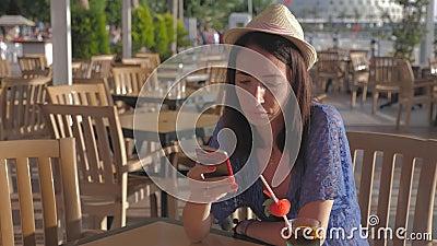 Κορίτσι κρατά ένα κοκτέιλ φρούτων σε μια τροπική καφετέρια κοντά στην παραλία Η έννοια της θερινής διακοπής στην παραλία απόθεμα βίντεο