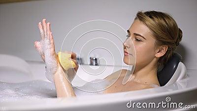 Κορίτσι ξαπλωμένο στο μπάνιο, πλύσιμο του σώματος με σφουγγάρι, καθημερινή διαδικασία ομορφιάς, φρεσκάδα φιλμ μικρού μήκους