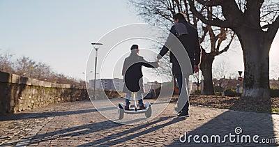 Κορίτσι παιδιών κορών που μαθαίνει τη segway οδήγηση με τη διδασκαλία μπαμπάδων στην πόλη Σύγχρονη μελλοντική τεχνολογία μεταφορώ