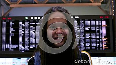 Κορίτσι που στέκεται μπροστά από τον πίνακα αφίξεων απόθεμα βίντεο