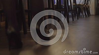 Κορίτσι στα μαύρα παπούτσια με τα τακούνια που περπατά στο σκοτεινό ξύλινο πάτωμα στο φραγμό φιλμ μικρού μήκους