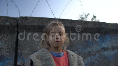 Κοριτσάκι με λασπωμένο πρόσωπο που στέκεται στο συρματόπλεγμα, παιδί πολέμου σε στρατόπεδο προσφύγων απόθεμα βίντεο