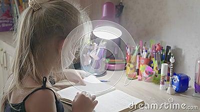 Κουρασμένη μαθήτρια διαβάζει ένα βιβλίο στο γραφείο της Εκπαίδευση και σχολική έννοια φιλμ μικρού μήκους