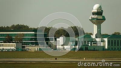 Κτήρια και πύργος ελέγχου αερολιμένων πέρα από την ελαφριά ομίχλη θερμότητας διαδρόμων φιλμ μικρού μήκους