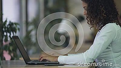 Κυρία Biracial που δακτυλογραφεί το ηλεκτρονικό ταχυδρομείο στο lap-top στο γραφείο, που χρησιμοποιεί τον υπολογιστή για την επικ φιλμ μικρού μήκους