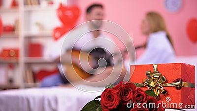 Κόκκινες κιβώτιο δώρων και δέσμη της κινηματογράφησης σε πρώτο πλάνο τριαντάφυλλων, αρσενική παίζοντας ρομαντική μελωδία κιθάρων απόθεμα βίντεο
