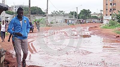 Κόκκινος βρώμικος δρόμος με το νερό σε μερικούς μολύβδους θέσεων σε ένα χωριό απόθεμα βίντεο