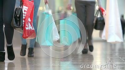 Κλείστε επάνω των ποδιών του αγοραστή που φέρνουν τις τσάντες στη λεωφόρο αγορών φιλμ μικρού μήκους