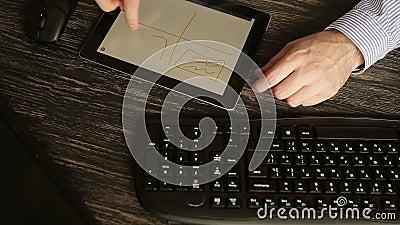 Κλείστε επάνω των χεριών με την ταμπλέτα στο ξύλινο γραφείο φιλμ μικρού μήκους