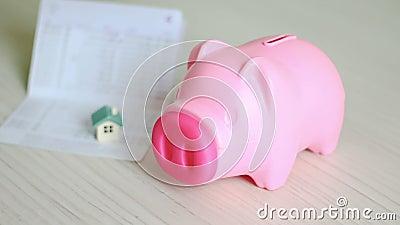 Κλείστε το αυξημένο χέρι του ατόμου που βάζει το νόμισμα χρημάτων στη ρόδινη piggy τράπεζα και θολώστε το βιβλιάριο τραπεζών σπιτ απόθεμα βίντεο