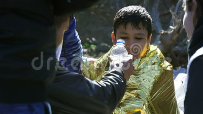 ΛΈΣΒΟΣ, ΕΛΛΑΔΑ - 5 ΝΟΕΜΒΡΊΟΥ 2015: Παγωμένος πρόσφυγας αγοριών στο θερμαίνοντας φύλλο αλουμινίου