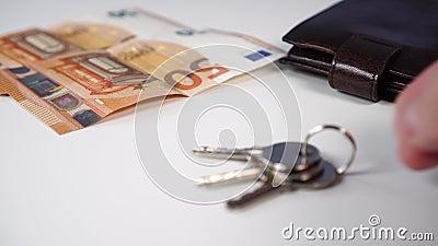 Λαμπερά νέα κλειδιά διαμερισμάτων με τραπεζογραμμάτια ευρώ και πορτοφόλι σε λευκό φόντο φιλμ μικρού μήκους