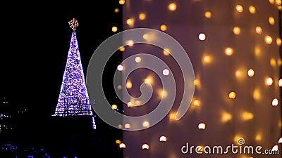 Λαμπρά διακοσμημένος με το χριστουγεννιάτικο δέντρο γιρλαντών που εξωραΐζει το κεντρικό τετράγωνο της πόλης απόθεμα βίντεο