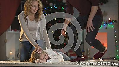 Λατρευτό κορίτσι πεσμένος κοιμισμένος κάτω από το χριστουγεννιάτικο δέντρο, ευτυχείς γονείς που έρχεται και που κτυπά φιλμ μικρού μήκους