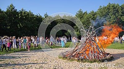 Λαϊκοί εορτασμοί σε υπαίθριο στο πράσινο ξέφωτο, πλήθος των ανθρώπων κοντά στη μεγάλη μεγάλη πυρά στη φύση, φωτεινή εορταστική πυ φιλμ μικρού μήκους