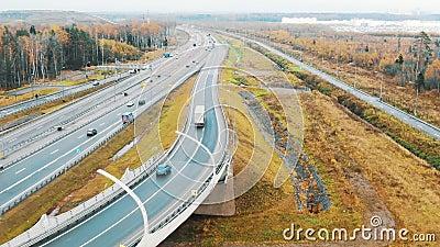 Λευκά φορτηγά οδηγούν στον αυτοκινητόδρομο ανάμεσα στη ροή των αυτοκινήτων, αεροφωτογραφία