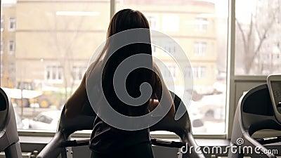 Μήκος σε πόδηα πίσω πλευρών σε σε αργή κίνηση ενός αθλητικού κοριτσιού με τη μακριά τρίχα brunette που τρέχει treadmill indoors φιλμ μικρού μήκους