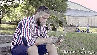 Μήνυμα γραψίματος νεαρών άνδρων στην ταμπλέτα, που κάθεται στα σκαλοπάτια πυροβολισμός ολισθαινόντων ρυθμιστών απόθεμα βίντεο
