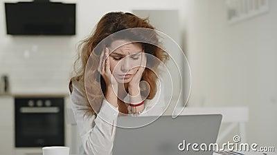 Ματαιωμένος λειτουργώντας υπολογιστής γυναικών στο σπίτι Νέο γυναικείο να κοιτάξει επίμονα lap-top στην κουζίνα απόθεμα βίντεο
