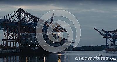 Μετάβαση από δύο μεγάλα πλοία μεταφοράς εμπορευματοκιβωτίων σε μικρότερα φορτηγά πλοία στο λιμάνι του Αμβούργου στο Dusk Πυροβολή απόθεμα βίντεο