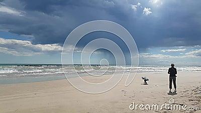 Μητέρα και κόρη περπατάνε σε μια αμμώδη παραλία την άνοιξη απόθεμα βίντεο