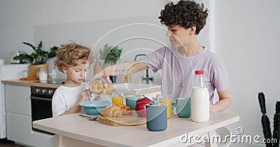 Μητέρα που νοιάζεται να βάζει δημητριακά σε παιδικό μπολ στην κουζίνα στο σπίτι κατά τη διάρκεια του πρωινού απόθεμα βίντεο