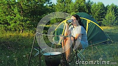 Μια γυναίκα στα γυαλιά ηλίου κοντά σε ένα τσάι κατανάλωσης πυρκαγιάς και θαυμασμός της φύσης φιλμ μικρού μήκους