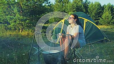 Μια γυναίκα στα γυαλιά ηλίου που κάθεται κοντά στην πυρκαγιά στη σκηνή, τσάι κατανάλωσης και θαυμασμός της φύσης απόθεμα βίντεο