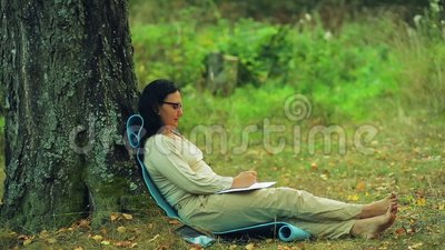 Μια γυναίκα στα γυαλιά κάθεται χωρίς παπούτσια κάτω από ένα δέντρο στο πάρκο και σύρει ένα μολύβι σε ένα σημειωματάριο απόθεμα βίντεο