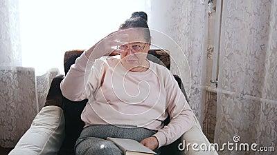 Μια ηλικιωμένη γυναίκα απολαμβάνει σε μια καρέκλα και μεγαλοφώνως στο υπόβαθρο του παραθύρου φιλμ μικρού μήκους