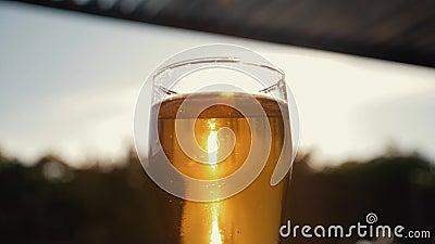 Μια κούπα της κρύας μπύρας ενάντια στον ουρανό και ένα κίτρινο ηλιοβασίλεμα στον ήλιο απόθεμα βίντεο