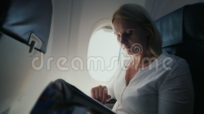 Μια νέα γυναίκα διαβάζει ένα περιοδικό στο πιλοτήριο ενός αεροπλάνου Άνεση και ψυχαγωγία στο ταξίδι απόθεμα βίντεο